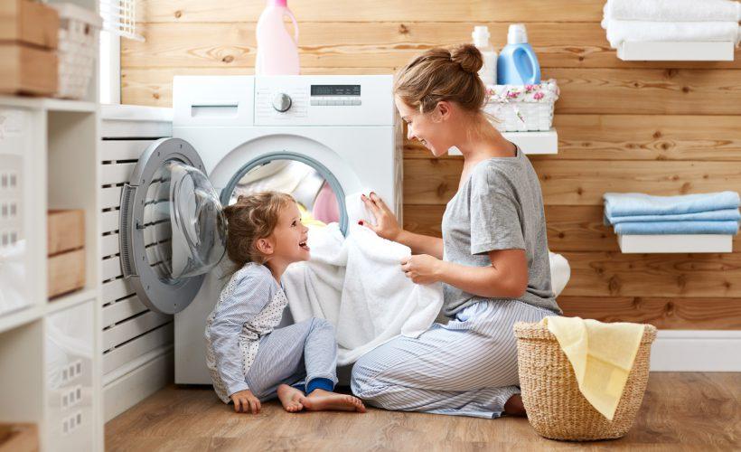 Çamaşır makinesine kıyafet koyan kadın ve kızı