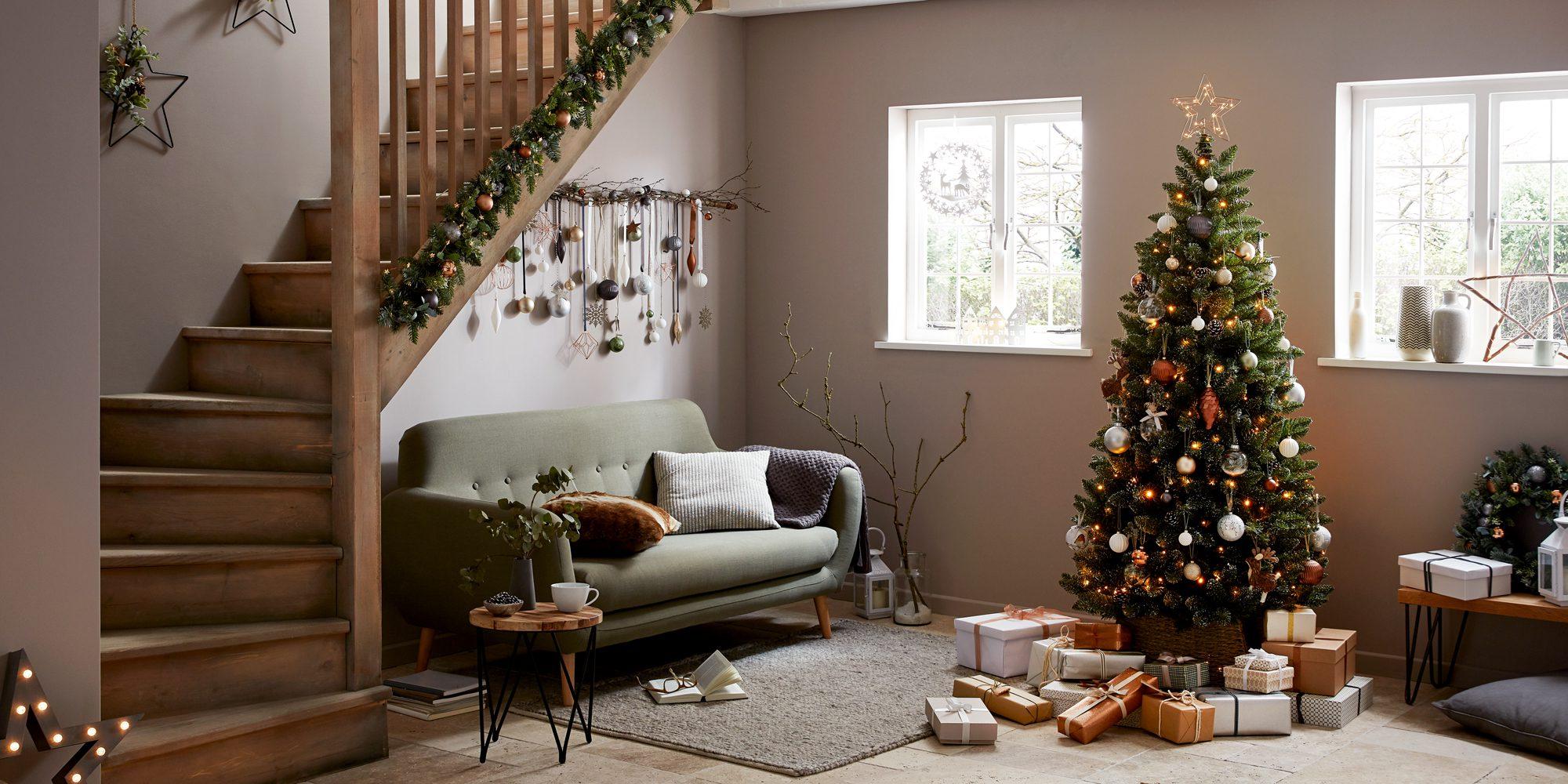 İki katlı evin salonunda duran süslenmiş yılbaşı ağacı