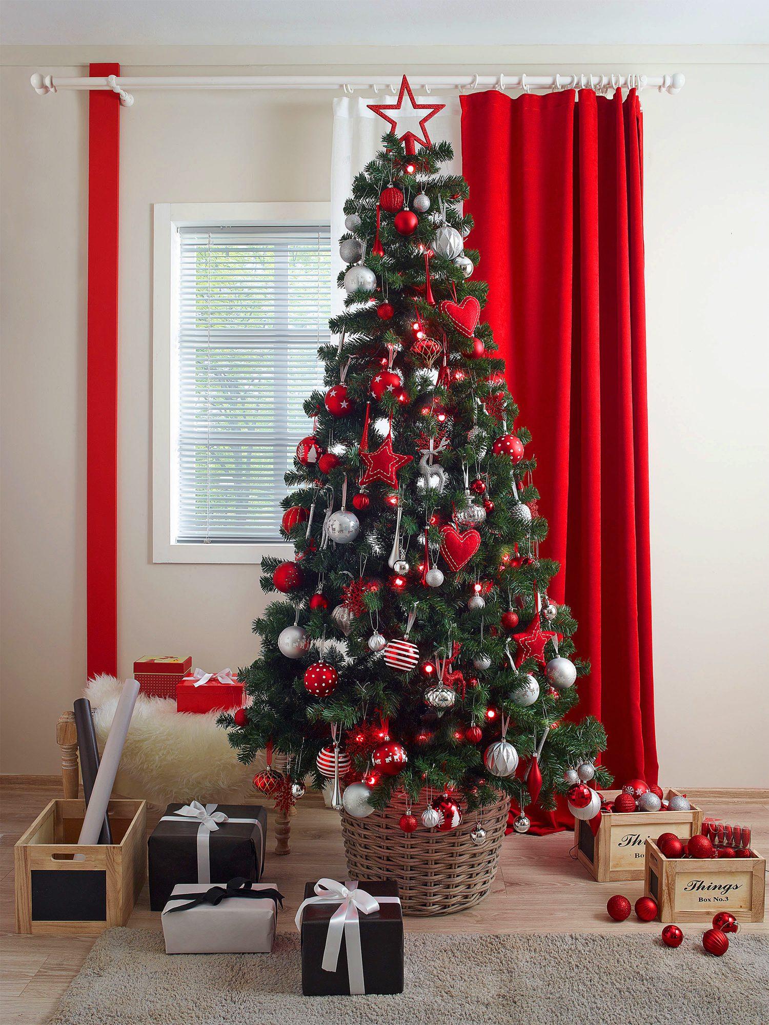 Kırmızı arka plana sahip süslenmiş yılbaşı ağacı
